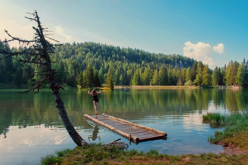 Visit Trentino Italy - jumping into an empty lake surrounded by forest