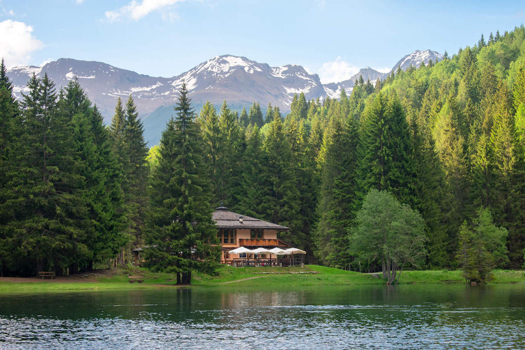 Visit Trentino Italy - alpine hut next to lake with forest and mountains