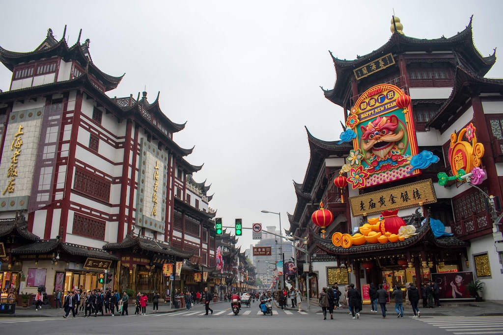 Shanghai Old City, busy street with large traditional buildings and colourful Chinese New Year decorations with a dragon