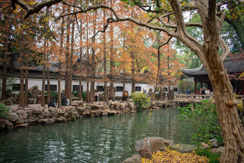 Shanghai Yu Garden, lake surrounded by trees with orange leafs and traditional Chinese building
