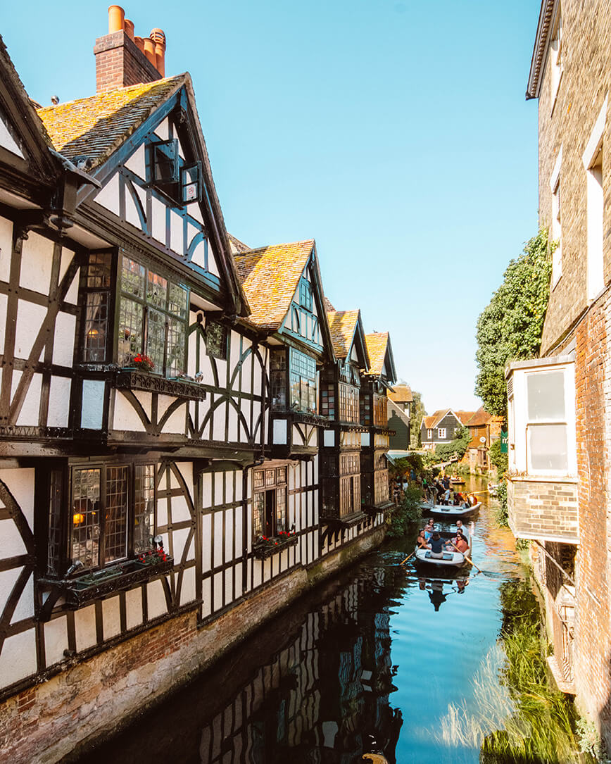 Weekend trips from London to historic towns, small boat going down river past thatched black and white tudor houses in Canterbury