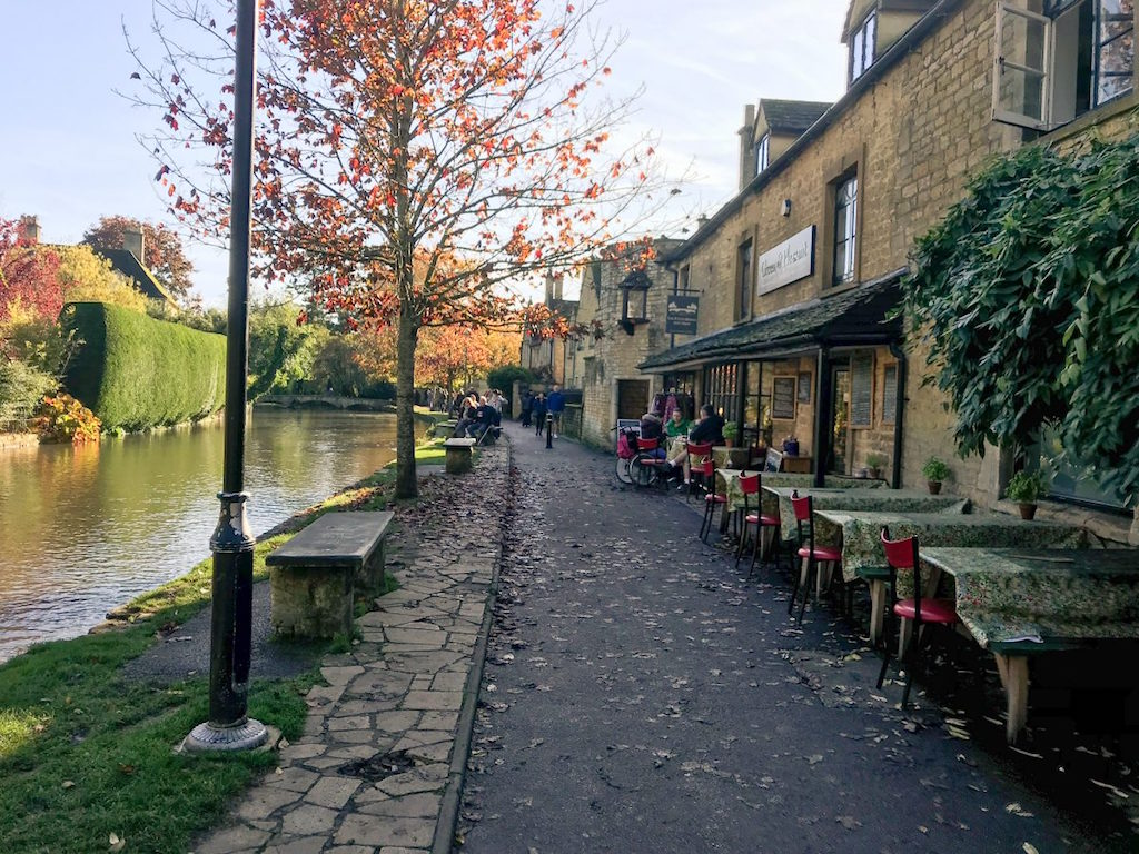 Weekend trips from London to historic towns, old stone houses next to river and orange trees in Cotswolds
