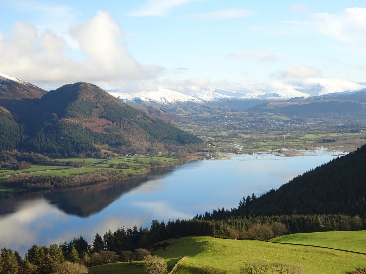 Weekend countryside breaks from London, lake surrounded by forest and mountains in the Lake District