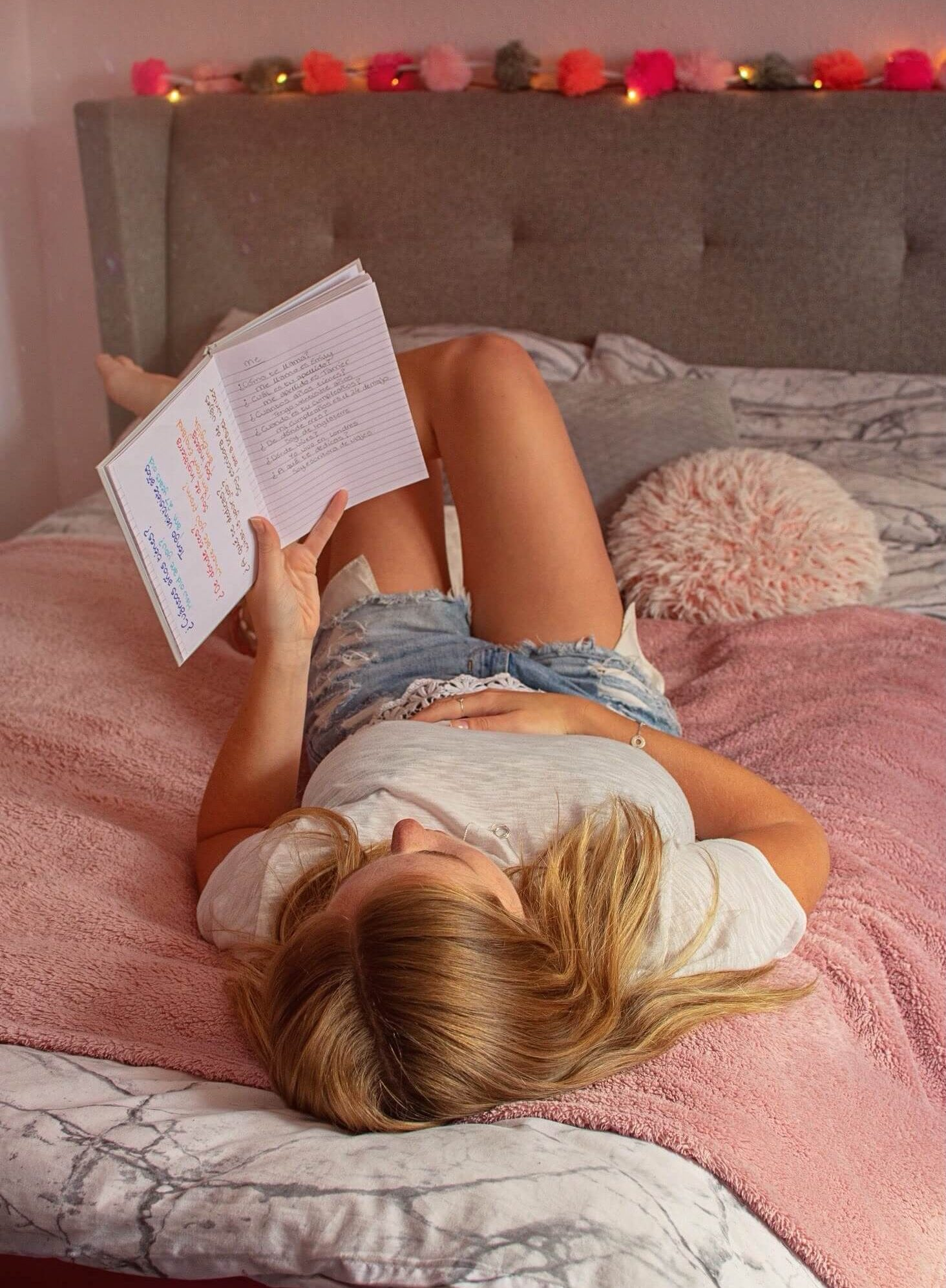 Girl on bed reading revision notes